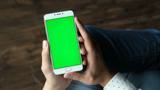 Le mani uomo tengono smartphone con display greenscreen