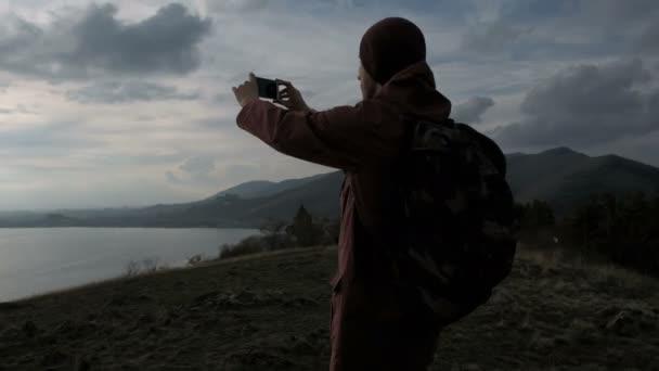 Zadní pohled na člověka s foto moře a hory