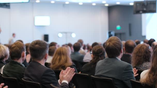 Group of businessmen applauding in auditorium