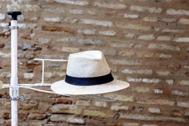 Panama hat on a display stand with a brick wall in the backgroun