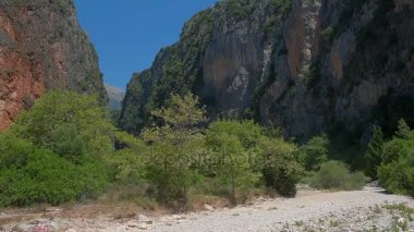 canyon panorama with steep walls in clear sunny day, at the bottom of a canyon trees and bushes, Albania