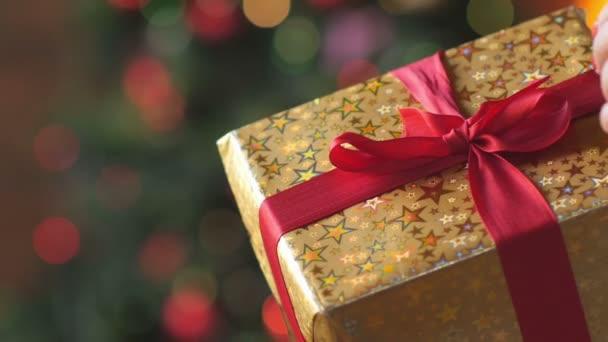 Ženské ruce otevřené dárkové krabice, odstraňte červenou stužkou z dárkové krabice. světlé sváteční girlandy na pozadí