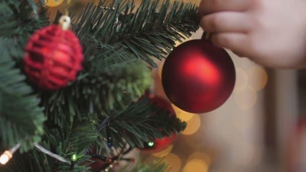 makrofotografie záběr ruky šťastné dítě visí koule na vánoční stromeček, děti zdobí vánoční strom.