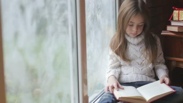 krásná holčička čte knihu sedí u okna