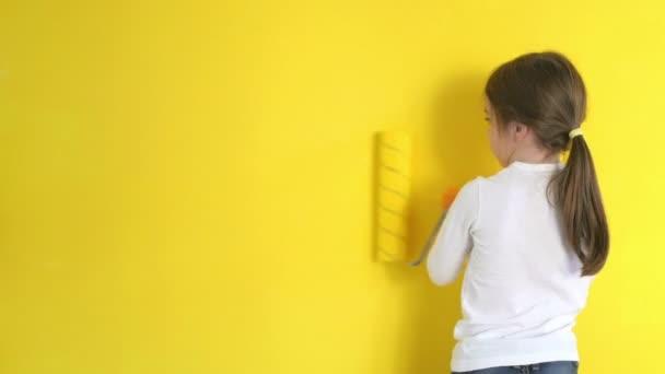 Grappige meisje schildert behoedzaam muren met een roller kamer