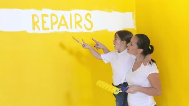 Máma s dcerou krasiad zdi v domě a bavit se, opravy v domě