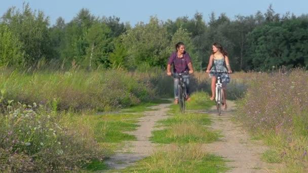 boldog pár lovaglás kerékpárok az esti parkban