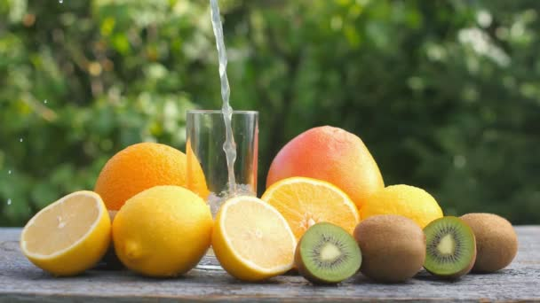 Freshly squeezed juice is poured into a glass, a set of ripe various fruits lies nearby. Multifruit. Diet Concept.