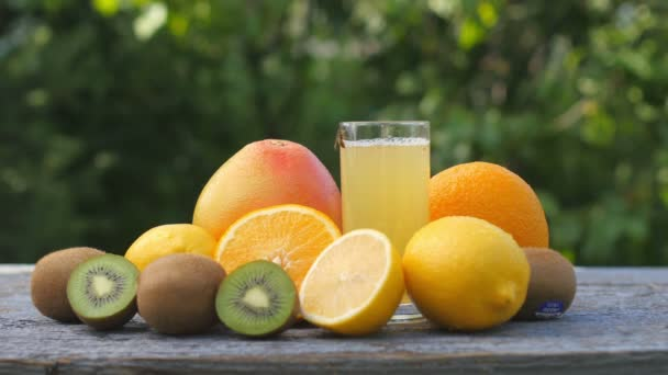A set of ripe fruits lies on the table. A bee crawls on a glass of fresh juice. Multifruit. Diet.