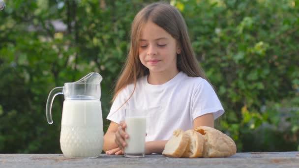 Roztomilé děvče nalévá čerstvé mléko do sklenice. Pít zdravé mléko a usmívat se. Chutné zdravé jídlo. Dieta