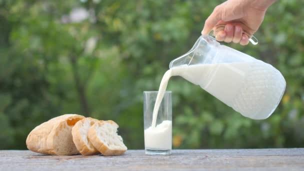 Mužská ruka nalévá mléko z džbánu do sklenice. Nedaleko na stole je bochník chleba.