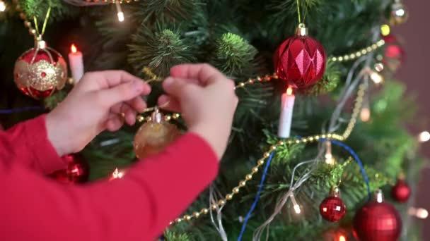 Dětské ruce zdobí vánoční stromek v místnosti s dekorativními kuličkami. Příprava na Vánoce a Nový rok. Dovolená