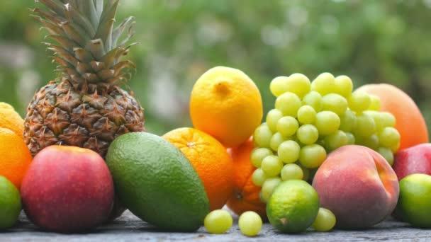 A férfi kéz egy pohár friss gyümölcslevet tesz az érett gyümölcs mellé. Gyümölcs készlet. Egészséges étel koncepció. Reggeli. 4k Uhd