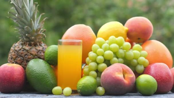 Szekrény érett gyümölcsök és egy pohár friss gyümölcslé egy fa asztalon. Gyümölcs készlet. Egészséges étel koncepció. Reggeli. 4k Uhd