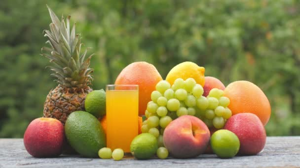 Closeup ripe fruits and a glass of fresh juice on a wooden table. Fruit set. Healthy food concept. Breakfast. 4K UHD
