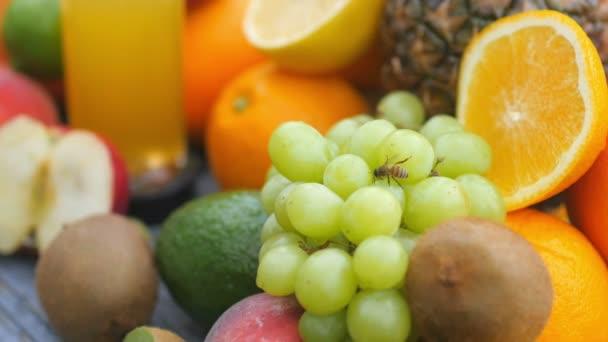 Fresh ripe fruits and a glass of fresh juice close-up. Pela crawls over the grapes. 4K UHD