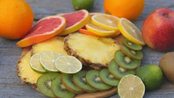 Close-up view from the top a variety of fruits, cut into slices, lie on a plate on a wooden table. Fruit set. Healthy food concept. Breakfast. 4K UHD