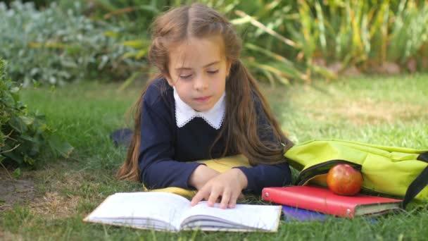 Škola. Holčičí školačka leží na trávníku a čte si knihu. Děti dělají domácí úkoly. 4k Uhd