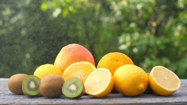 Különböző érett gyümölcsök közeli készlete egy fából készült asztalon. Finom egészséges gyümölcsök. Citrusfélék. Egészséges étel koncepció. 4k
