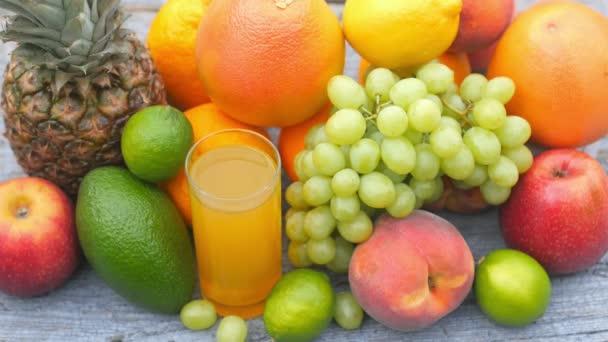 Egy pohár friss gyümölcslé közelsége áll a sok gyümölcs között egy fából készült asztalon. Gyümölcs készlet. Egészséges étel koncepció. Reggeli. 4k Uhd