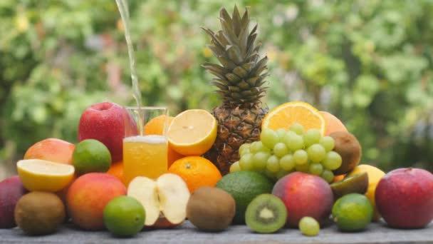 Detailní žlutý ovocný džus se nalije do sklenice. Různé druhy ovoce na dřevěném stole v zahradě. Sklenici čerstvého pomerančového džusu, sodovku. Lahodné zdravé jídlo.