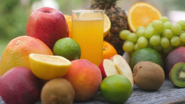 Közelről egy pohár sárga lé és sok gyümölcs egy fa asztalon a kertben. Különböző érett gyümölcsök. Finom egészséges élelmiszer..