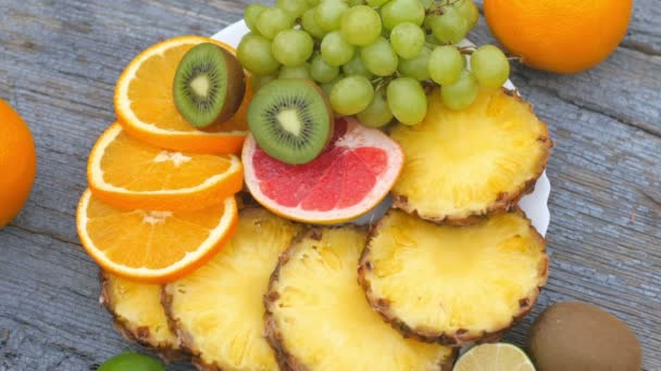Detailní záběr různých druhů čerstvého ovoce nakrájeného na plátky na talíři. Zralé ovoce na dřevěném stole. Ovoce se otáčí 360 na talíři. Koncept zdravé stravy