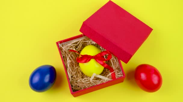 Easter celebration. A yellow Easter egg tied with a red ribbon lies in a red gift box on a yellow background. Easter background