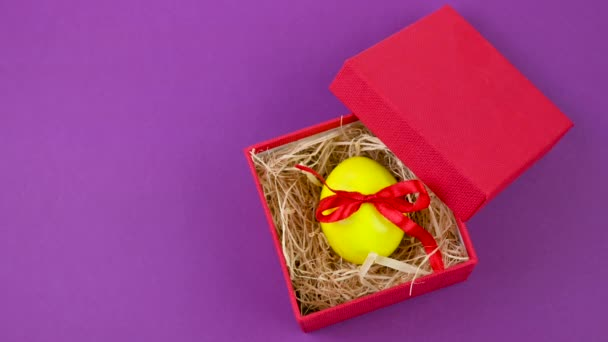 Easter celebration. A yellow Easter egg tied with a red ribbon lies in a red gift box on a gray background. Easter background