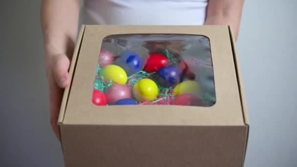 Eine Frau öffnet und zeigt eine Schachtel mit bunten Ostereiern. Osterdekoration. Hintergrund zum Osterkonzept.