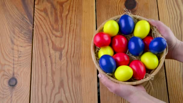 Easter celebration. Female hands hold a plate with colorful easter eggs over a wooden table. Easter background