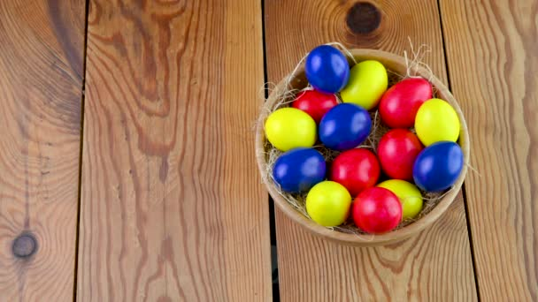 Colorful easter eggs lie on a yolk in a basket on a wooden table. Easter decorations. Easter concept background.