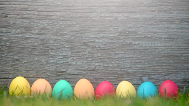 Easter celebration. Colorful easter eggs on the lawn on a wooden background. Easter concept background.