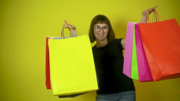 Portré egy boldog fiatal lányról színes papírzacskókkal, sárga stúdió háttérrel. Az értékesítésre és az árengedményekre vonatkozó elképzelések.