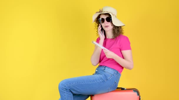 Vonzó fiatal lány napszemüvegben ül egy bőröndön egy jegyet, és használ egy okostelefon izolált sárga narancs háttér a stúdióban. útiterv.