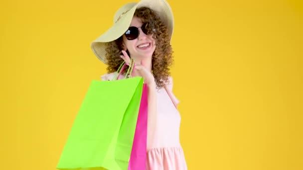 Portrét šťastné mladé dívky v klobouku ve slunečních brýlích s barevnými papírovými sáčky izolovanými na žlutém pozadí studia. Koncepty pro prodej a slevy.