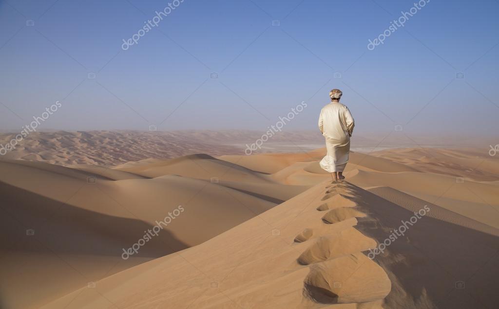 Man in kandura in a desert at sunrise