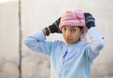 omani boy fixing his head scarf