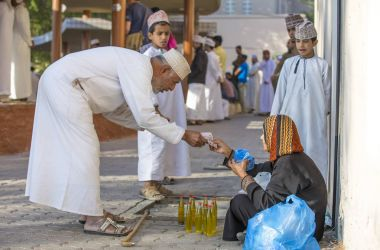 man is buying moringa oil at the market
