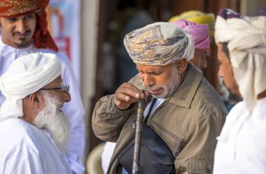 omani man selling a hunting rifle at a market