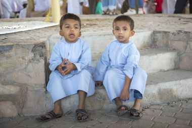brothers in traditional clothing in a market in Nizwa