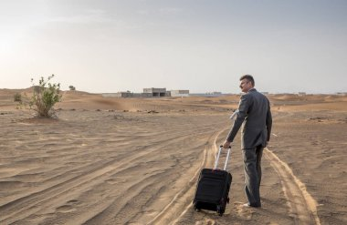 businessman in  a desert with a suitcase