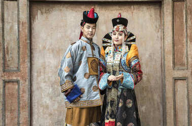 mongolian couple in traditional outfit near old Temple in Ulaanbaatar in traditional outfit near old Temple in Ulaanbaatar