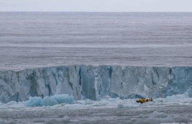 people traveling in zodiac between icebergs of Svalbard