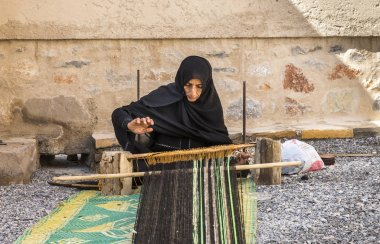 Nizwa, Oman, February 2, 2018: omani woman weaving a carpet
