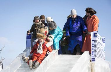 Hatgal, Mongolia, 3rd March 2018: mongolian boy on a slide of ice on a frozen lake Khuvsgul during a ice festival in a winter