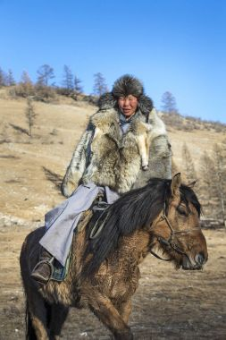mongolian man wearing a wolf skin jacket, riding his horse in a