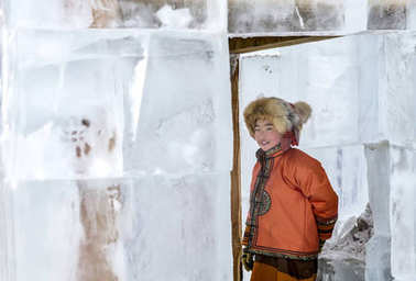 Hatgal, Mongolia, 3rd March 2018: mongolian boy inside an ice structure on a frozen lake Khuvsgul during a ice festival in a winter