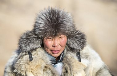 portrait of a mongolian man dressed in traditional wolf skin clothing