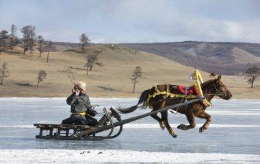 Hatgal, Mongolia, 2nd March 2018: people riding on a sledge on a frozen lake Khuvsgul